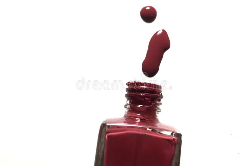 Red color spill out of bottle nail color ink. The rate color spill out of bottle nail royalty free stock image