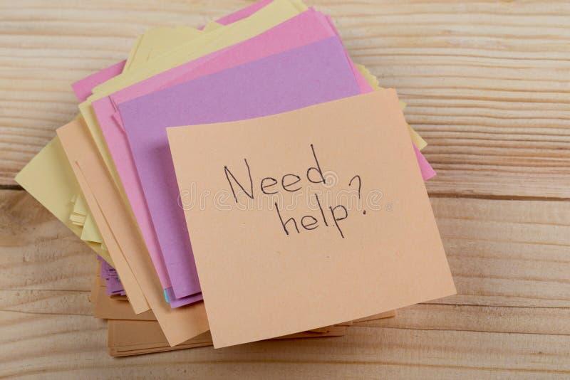 Ratekonzept - Aufkleber mit den Wörtern ' Bedarf help' auf hölzernem Hintergrund Konzept des Bittens um Hilfe lizenzfreie stockfotos