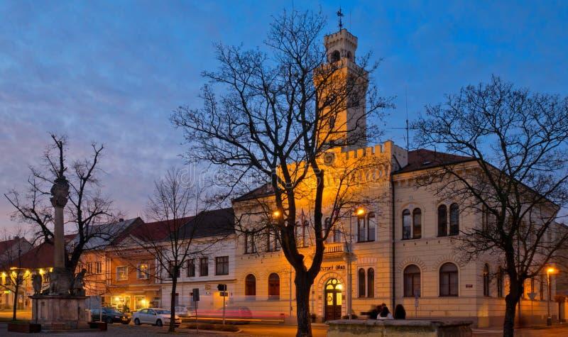 Rathaus mit Verkehr in der Kleinstadt Postoloprty bei Dämmerung im Winter lizenzfreies stockfoto