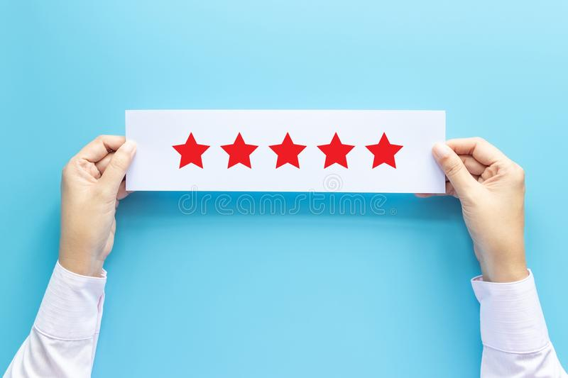 Rating and feedback concept. customer holding paper with satisfied review by give five star for service experience stock images