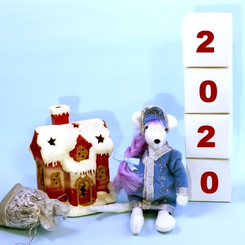 Rato branco bonito em um claro - donzela azul da neve do terno no centro do quadro perto da casa coberto de neve e dos cubos com  fotos de stock royalty free
