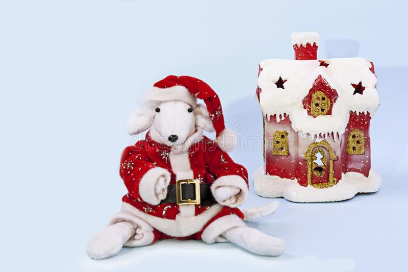 Rato branco bonito em um terno vermelho de Santa Claus no centro do quadro perto da casa coberto de neve em um claro - fundo azul foto de stock royalty free