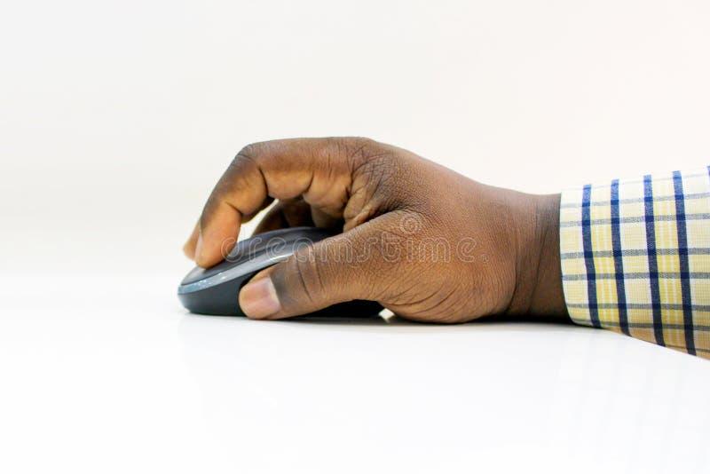 Rato do computador da terra arrendada da mão do homem africano contra o fundo branco imagem de stock