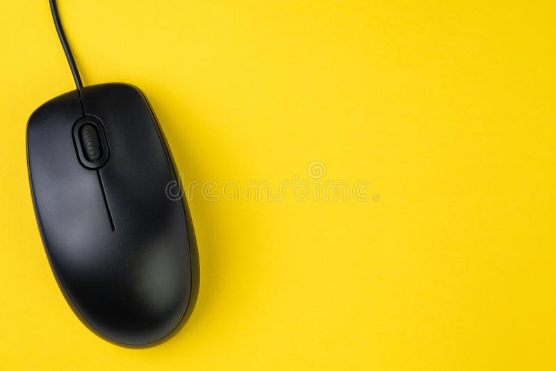 Rato preto do computador com roda e cabo do rolo na tabela amarela fotos de stock royalty free
