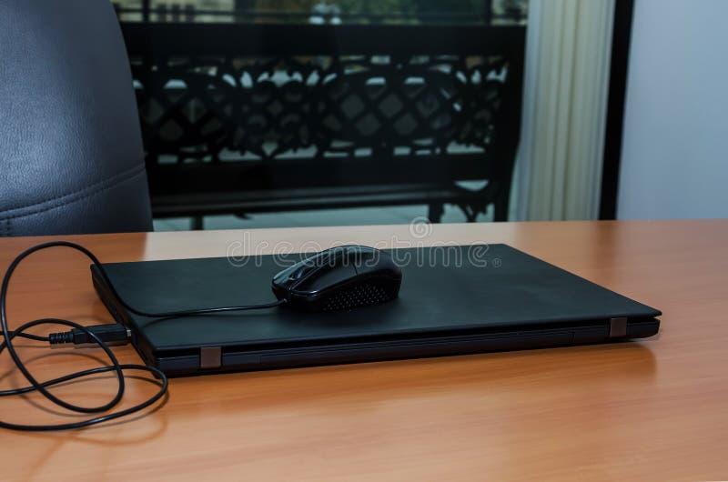 Rato preto do portátil e do computador em uma tabela de madeira no escritório foto de stock