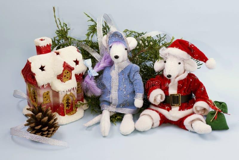 Ratos brancos bonitos em um terno de Santa Claus e da donzela da neve perto de um ramo de um thuja e de uma casa coberto de neve  imagem de stock royalty free