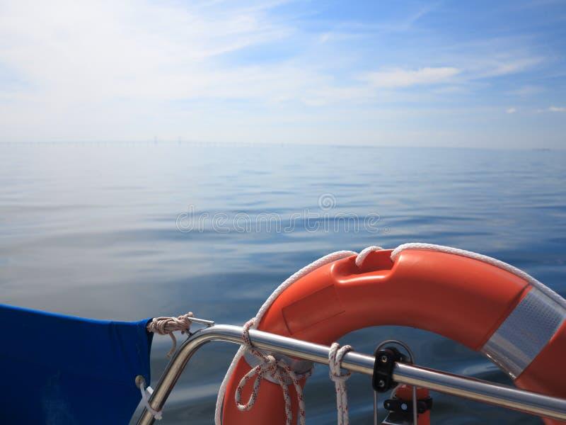 Ratowniczy czerwony lifebuoy na żagla i niebieskiego nieba morzu obrazy royalty free