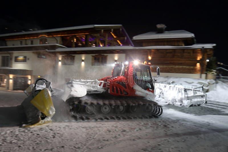 Ratrack雪修饰机器倾斜为滑雪场的滑雪者做准备在山在夜 免版税图库摄影