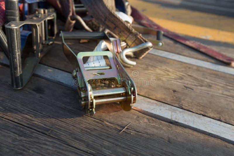 Ratschen-Verzurren, das auf Holz sitzt lizenzfreies stockfoto