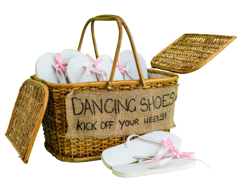 Rattan basket with white flip-flops with pink ribbon bows for guests, with a writing DANCING SHOES. KICK OFF YOUR HEELS! stock photos