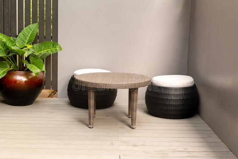 Rattan corner round chair on wooden floor and plant outdoor. stock photography