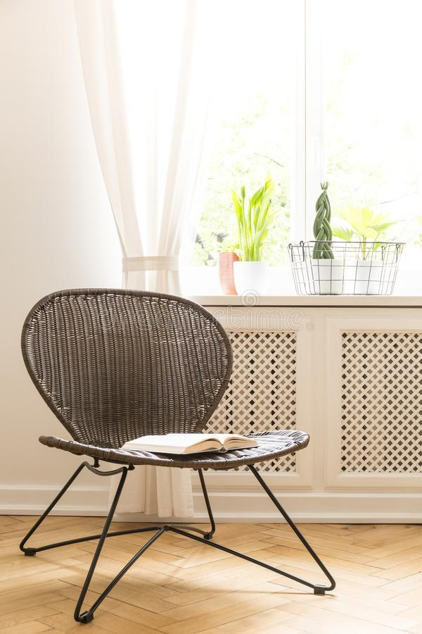 A rattan and metal chair with an open book on a seat standing on a wood flooring against a white wall and a sunny window in a livi royalty free stock photography