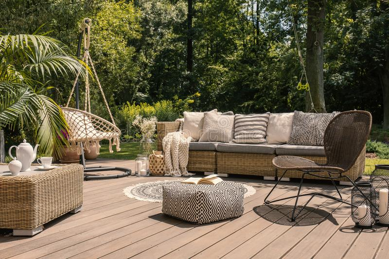 A rattan patio set including a sofa, a table and a chair on a wooden deck in the sunny garden. Concept royalty free stock images