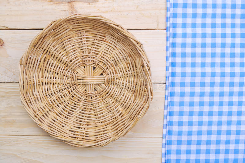 Rattan plate or basket on wooden table. And tablecloth on table wood plank made for background royalty free stock image
