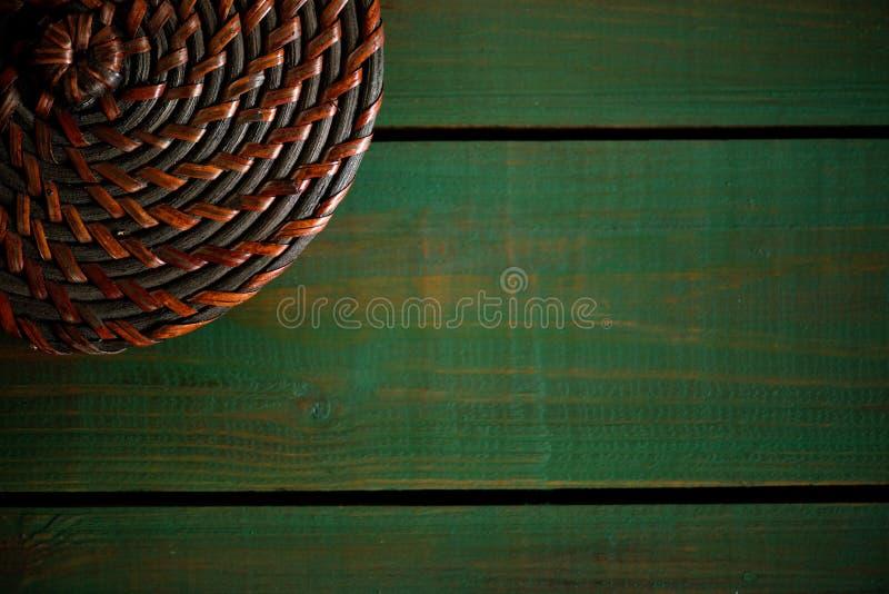 Rattan round dekiel na drewnianych zielonych deskach Jaskrawy jako tło tekstury winieta - zielona drewniana struktura obrazy stock