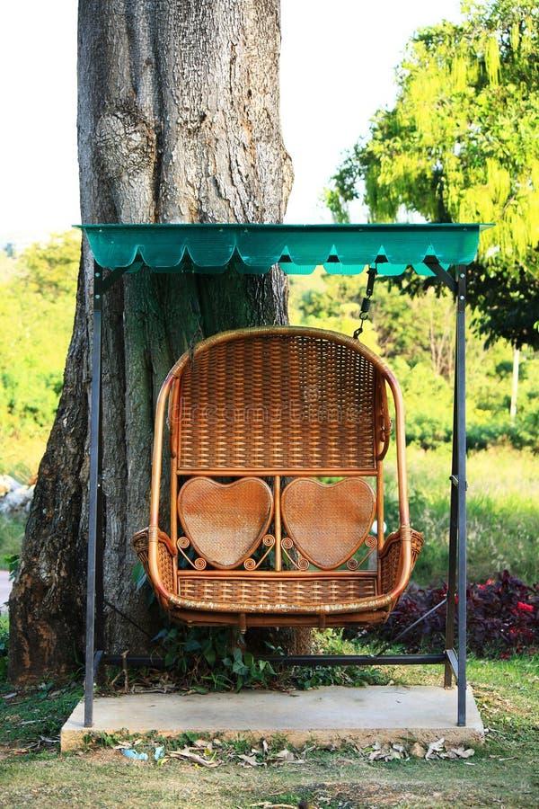 Rattan Swing Bench In Garden Stock Images
