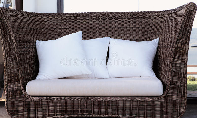 Rattan wicker sofa with pillows royalty free stock photos