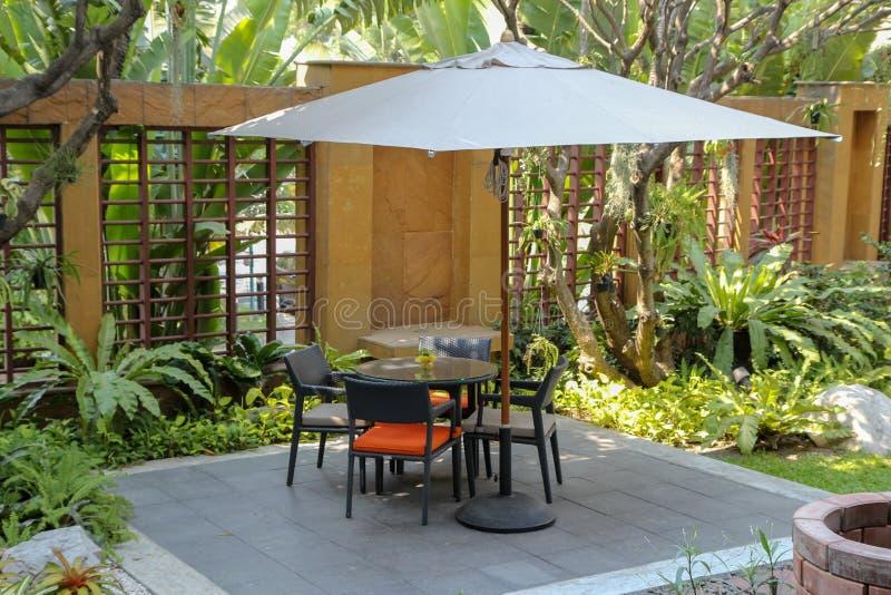 Rattangartentisch und -stühle, den Gartenstuhl speisend im Freien im Garten, Möbel im modernen Patio lizenzfreie stockbilder