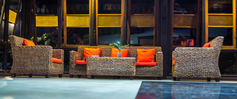 Rattansofa mit orange Kissen in der Lobby eines Hotels lizenzfreies stockbild