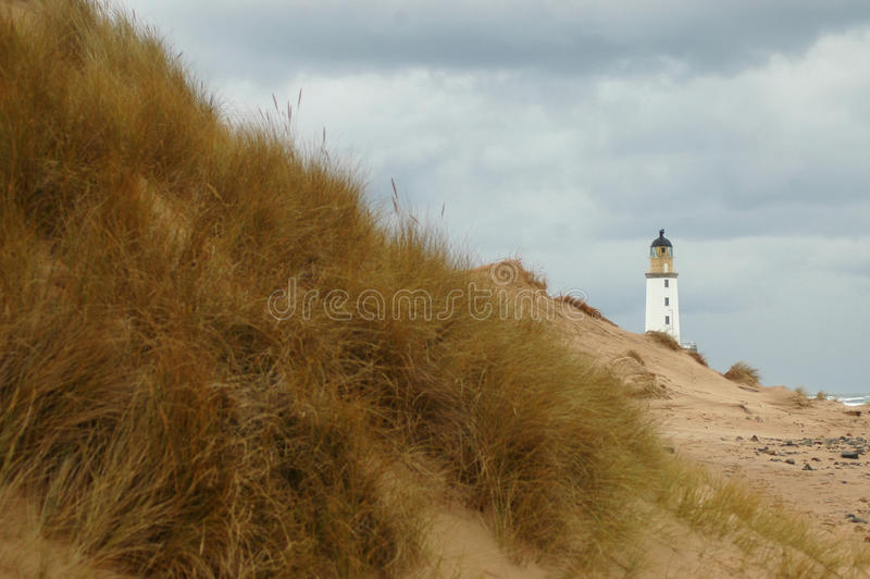 Lighthouse behind sand dunes royalty free stock photo