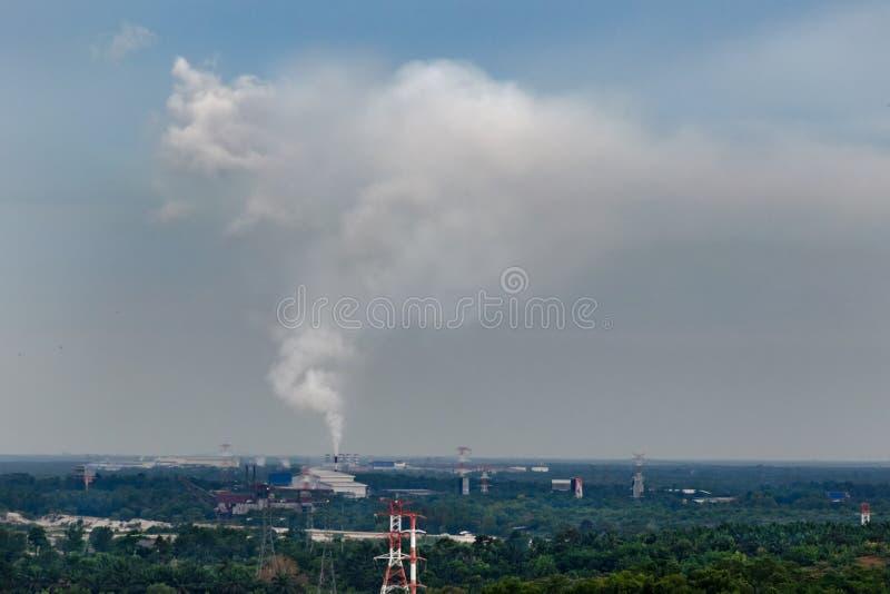 Rauch von Kraftwerk ` s Rohr steigt hoch in Himmel gegen Hintergrund des grünen Dschungelwaldes stockbilder