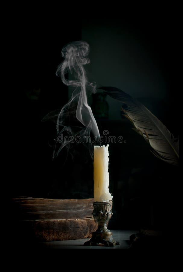 Rauchen über der Kerze, die auf dem Tisch mit altem gebranntem b steht lizenzfreie stockbilder