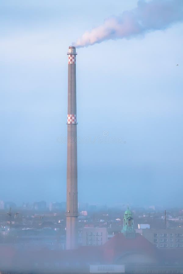 Rauchen Sie von einem Fabrikkamin in einem dunstigen städtischen Himmel stockfotos