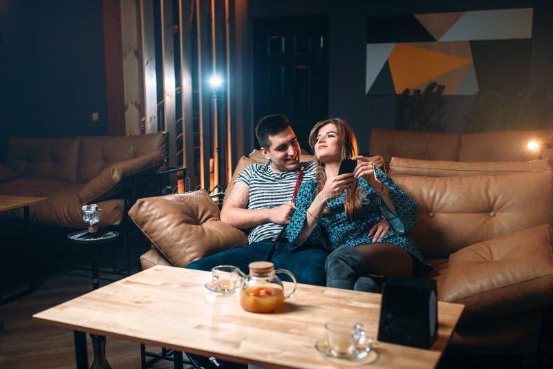 Rauchende Huka der jungen Paare auf Ledercouch stockfoto