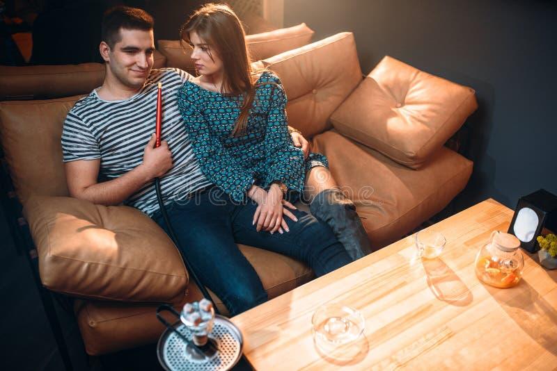 Rauchende Huka der jungen Paare auf Ledercouch stockbilder