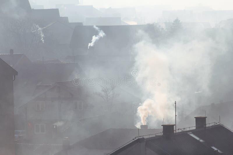 Rauchende Schlote an den Dächern von Häusern strahlen Rauch, Smog bei Sonnenaufgang, Schadstoffe eintragen Atmosphäre aus Apokaly lizenzfreies stockbild