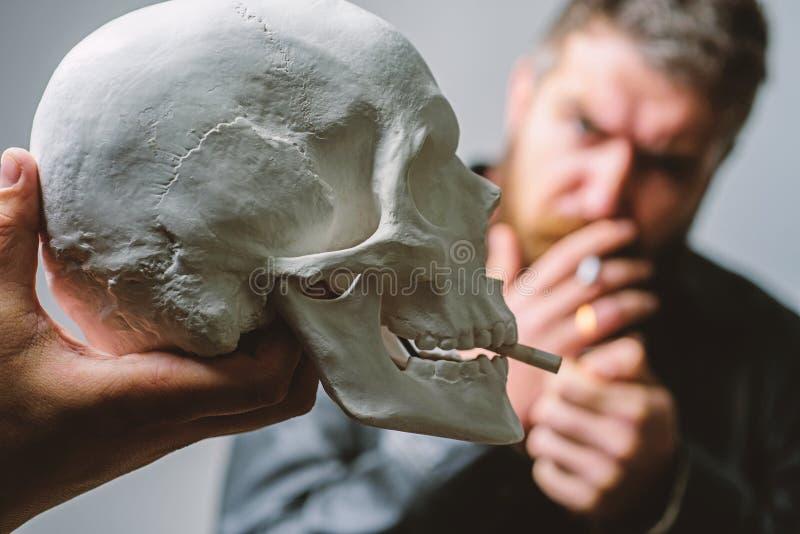 Rauchende Zigarette des Mannes nahe menschlichem Sch?delsymbol des Todes Sch?dliche Gewohnheiten Rauchende UrsachenGesundheitssch stockfotografie