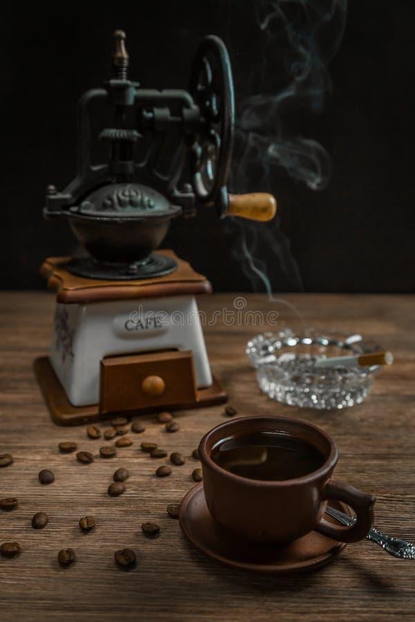 Rauchende Zigarette, ein Aschenbecher und ein Tasse Kaffee lizenzfreies stockbild