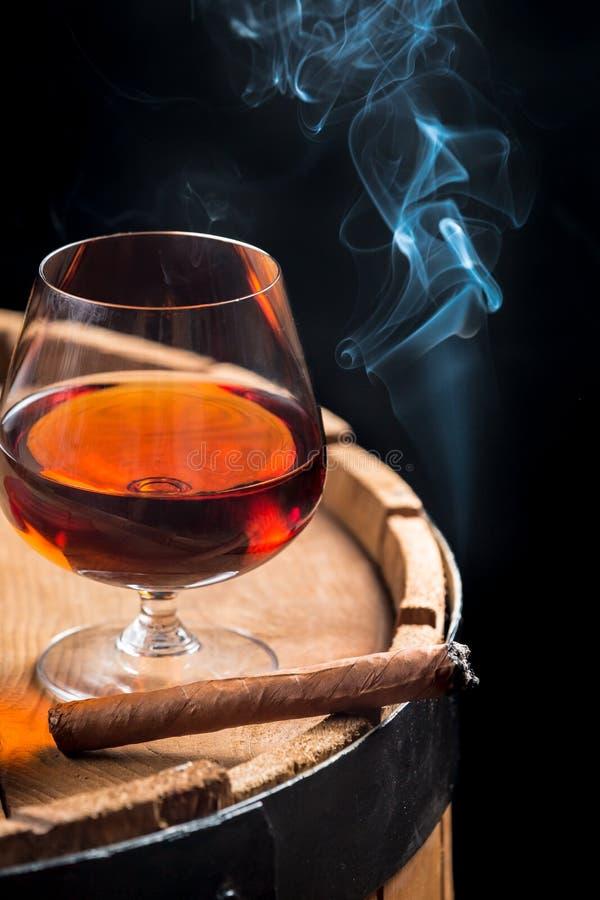 Rauchende Zigarre und hölzernes Weinbrandfaß lizenzfreie stockfotos