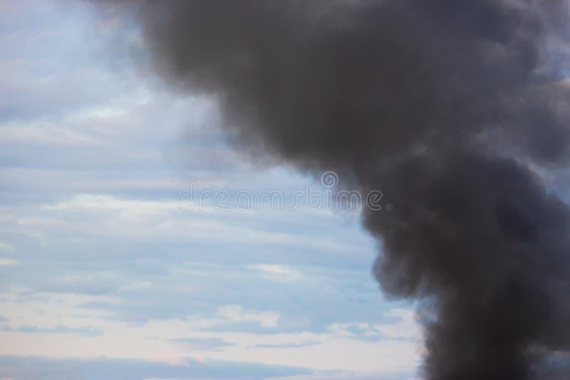 Rauchender Fabrikkamin, schwerer schwarzer Rauch auf dem Himmel lizenzfreies stockbild