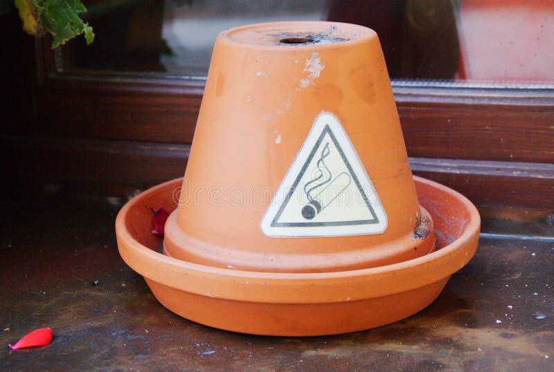 Rauchendes erlaubtes Zeichen in Form des Dreiecks auf dem keramischen Topf auf dem Fensterbrett lizenzfreies stockfoto