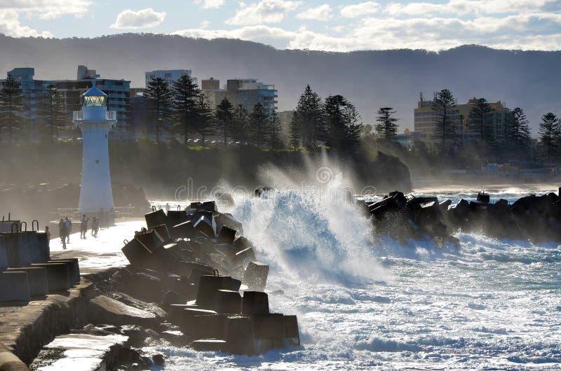 Raue Meere nähern sich Leuchtturm breakwall stockbild
