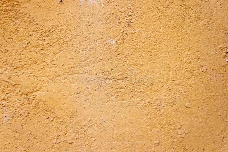 Raue rustikale schäbige Beschaffenheit des Hintergrundes der alten Wand mit gelbem gebrochenem Gips stockfoto