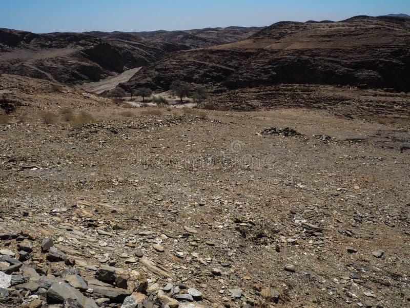Rauer Felsengebirgsbeschaffenheits-Landschaftshintergrund der einzigartigen Geografie Namibischer Wüste mit aufspaltendem Steinbo stockbild