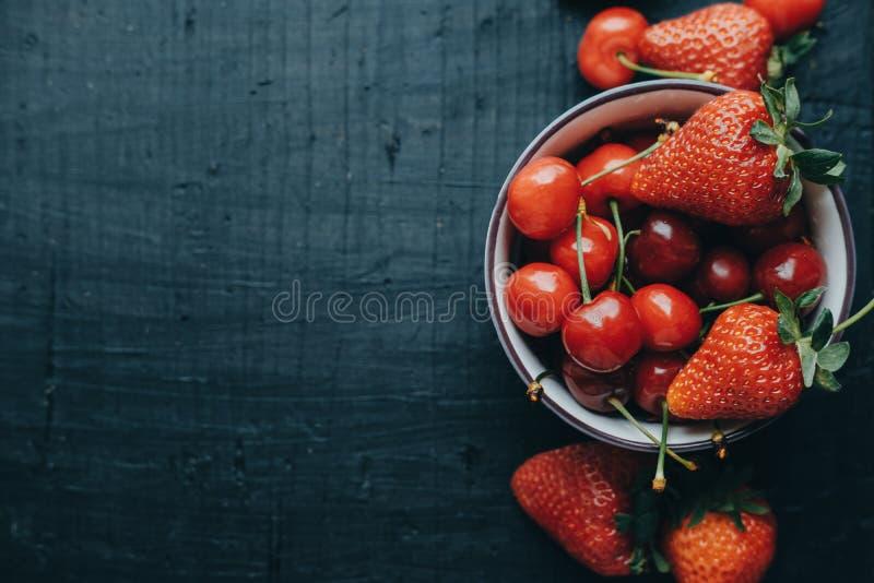 Raum für Text, frische Kirschen und Erdbeeren auf dem Schwarzen flehen an lizenzfreie stockbilder
