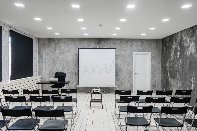 Raum für Vortrag mit vielen dunklen Stühlen Wände sind, Dachbodeninnenraum weiß Auf ist dort eine Tür auf stockfoto