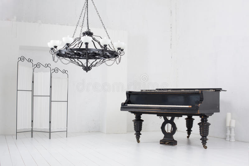 Raum mit einem Klavier, einem faltenden Schirm und einem Leuchter lizenzfreies stockfoto