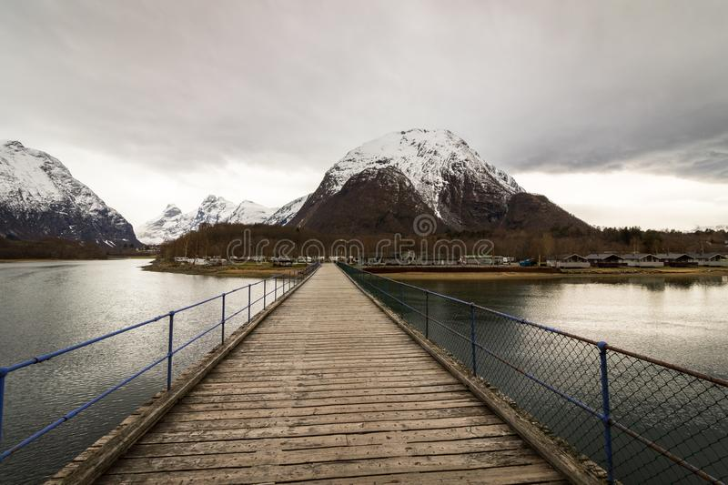 Rauma, Romsdalen in Norway - April, 19, 2017: A wooden bridge over the Rauma river leads to Andalsnes Camping, located. Close to Trollveggen and Trollstigen royalty free stock photos