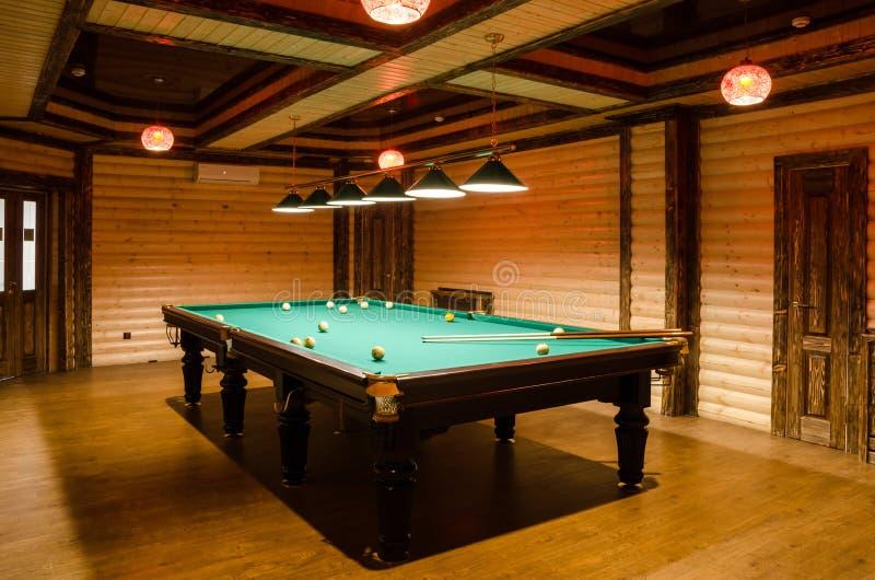 Raumbillard verziert im dunklen Holz mit niedrigen Lampen, Billardtisch mit grünem Stoff stockbild