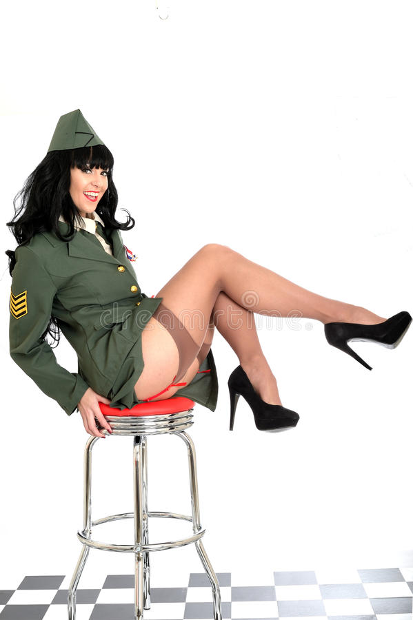 Raunchy Flirtatious Young Vintage Pin Up Model In Military Uniform and Stockings royalty free stock photo