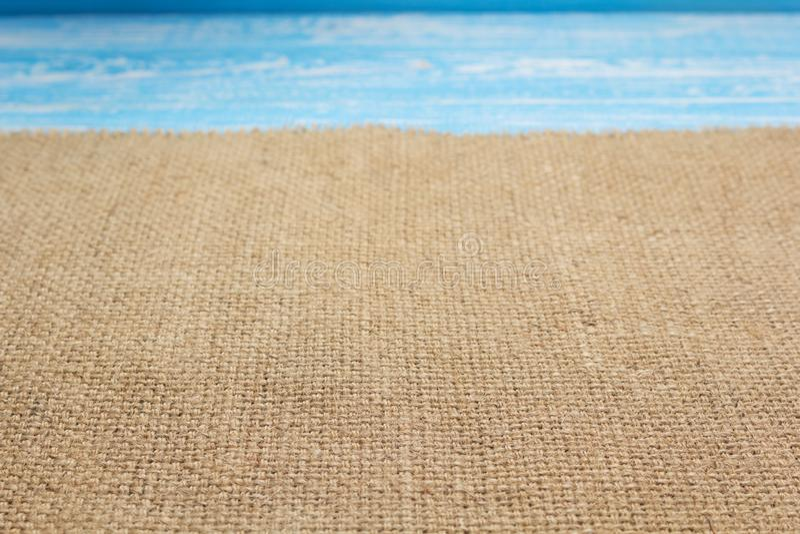 Rausschmissstoff des Leinwandgroben sackzeugs auf hölzernem Hintergrund lizenzfreie stockfotos