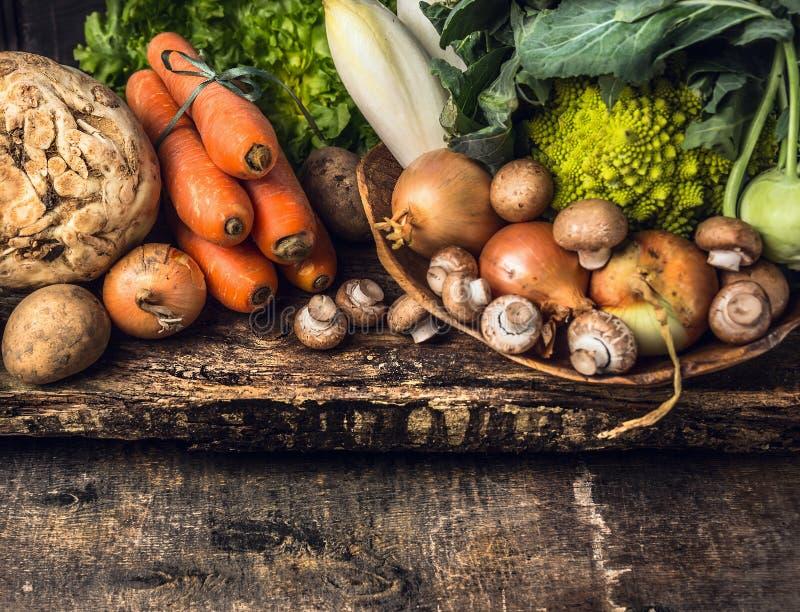 Rauwe groenten en eetbare wortel divers op donkere houten rustieke achtergrond stock foto's