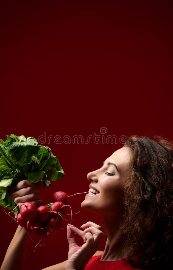Ravanello fresco della tenuta della donna con le foglie verdi stare Concetto sano di cibo su fondo rosso per la storia del instag immagine stock