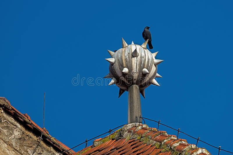 Raven on top of the house. Raven on a lightning rod on top of the house stock photography