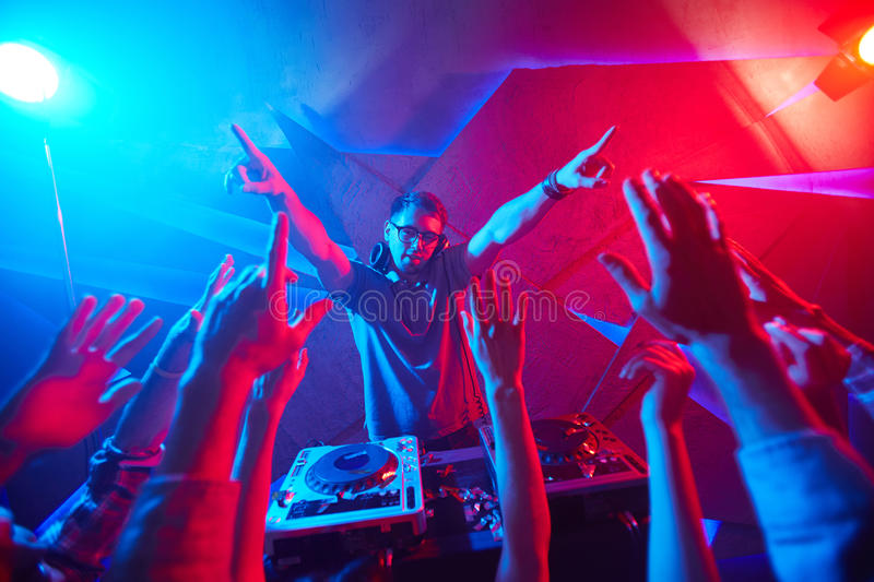 Raving dancers. Deejay and crowd raving in disco club royalty free stock images
