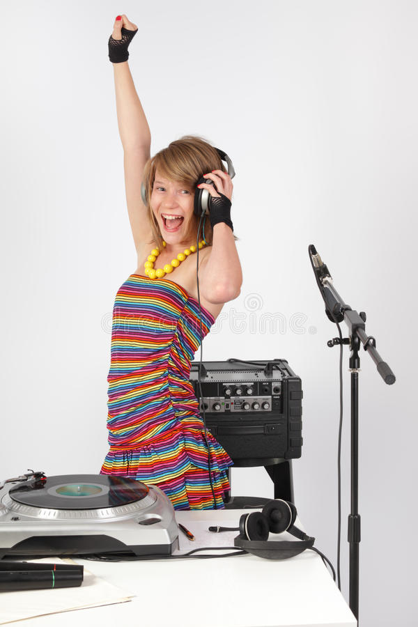 Raving DJ girl. Raving deejay DJ 13-year old girl in studio or at a disco party with equipment and a turntable shouting and having fun stock photo